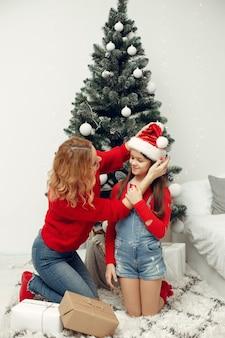 Les gens réparent pour noël. mère jouant avec sa fille. la famille se repose dans une salle de fête. enfant dans un pull rouge.