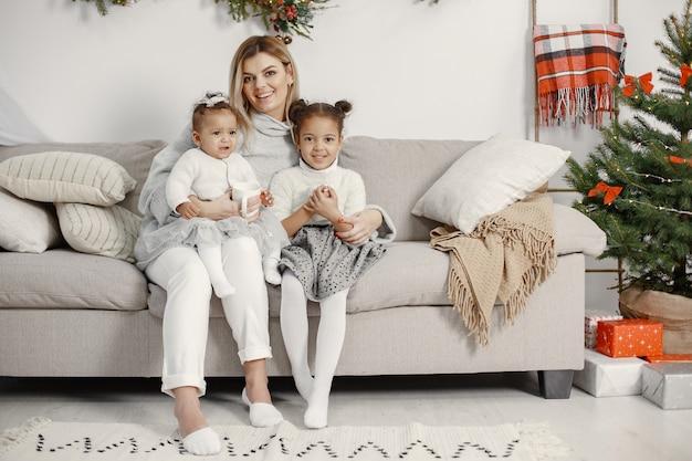 Les gens réparent pour noël. mère jouant avec ses filles. la famille se repose dans une salle de fête. enfant dans un pull-over.