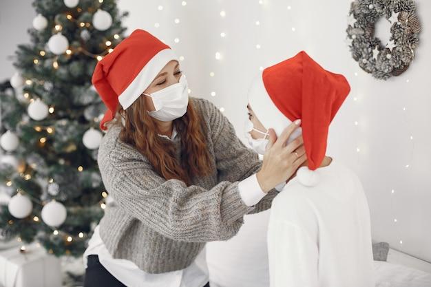 Les gens réparent pour noël. thème du coronavirus. mère jouant avec son fils. garçon dans un pull blanc.