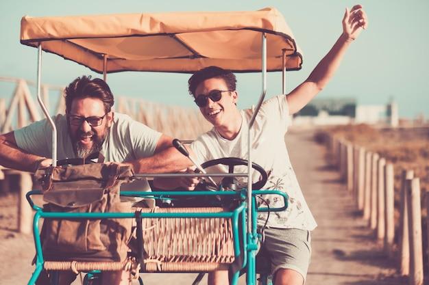 Les gens s'amusent avec le père et le fils de la famille d'âges différents en riant et en profitant d'un vélo d'été