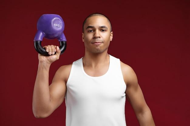 Les gens, la santé, les sports, le fitness et la dynamophilie. confiant fort jeune powerlifter armé afro-américain soulevant des haltères 12 kg tout en travaillant dans une salle de sport, posant sur fond de mur de studio rouge blanc
