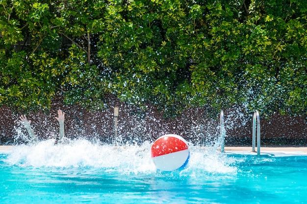 Les gens sautent à l'intérieur de la piscine en jouant avec un ballon gonflable. concept d'été et de vacances