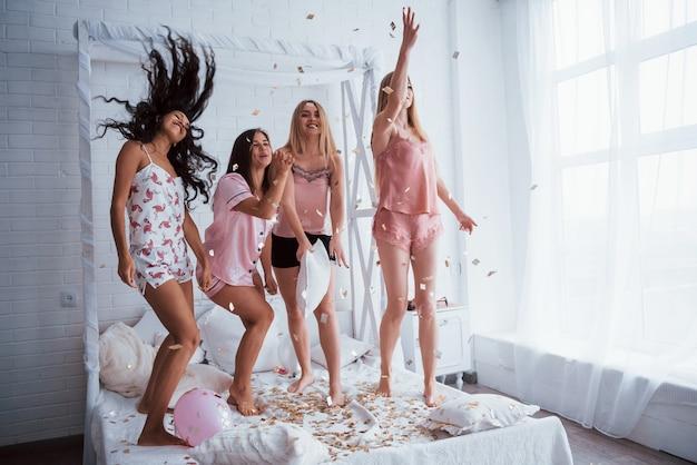 Ces gens savent faire la fête. confettis dans l'air. les jeunes filles s'amusent sur le lit blanc dans une belle chambre