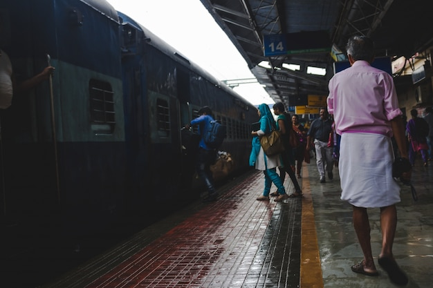 Les gens se précipitent à bord d'un train en tant qu'homme dans une chemise rose marche par