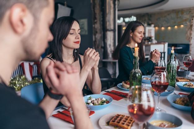 Les gens se tenant la main en priant le concept de célébration de thanksgiving.