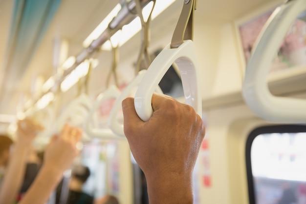 Les gens se tenant sur une poignée de train.