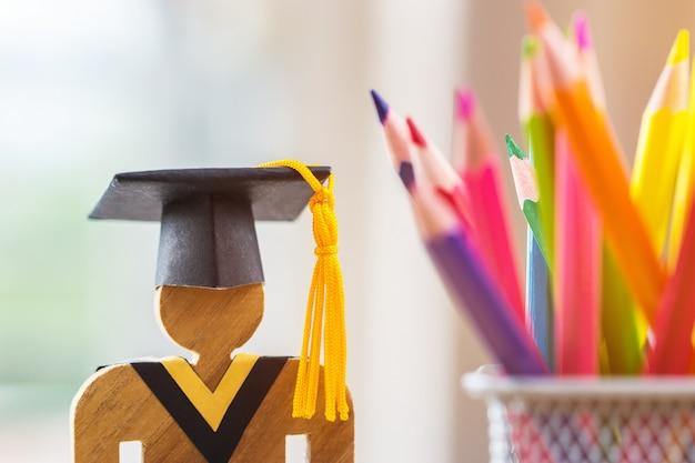 Gens signe bois avec graduation célébrer chapeau, boîte crayon flou