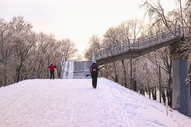 Les gens skient dans un parc enneigé