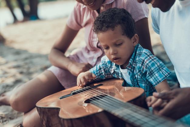 Les gens sont assis avec une guitare acoustique sur la rive sablonneuse.