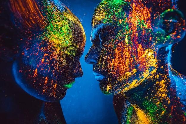 Les gens sont colorés en poudre fluorescente. un couple d'amoureux dansant dans une discothèque.