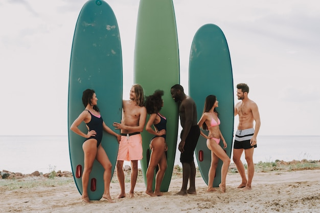 Les gens sont debout plage détient surfs filles en maillot de bain