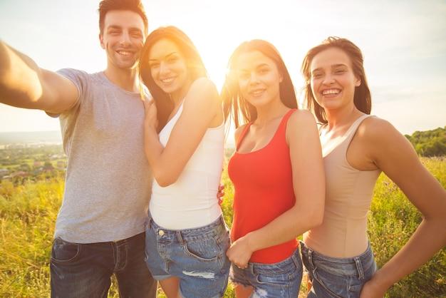 Les gens souriants font un selfie sur fond de soleil