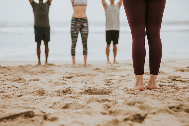 Gens sportifs s'étirant à la plage