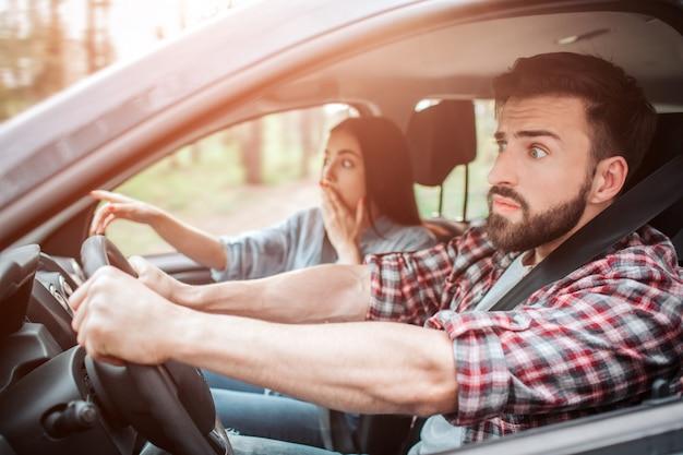 Des gens stupéfaits sont assis dans la voiture et regardent droit devant. ils sont frustrés. la fille couvre sa bouche d'une main et pointe vers l'avant avec une autre.