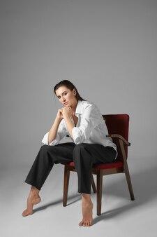 Les gens, le style, la mode, les vêtements et le concept d'intérieur. portrait vertical de l'élégante belle jeune femme aux pieds nus dans les vêtements formels pour hommes, assis sur une chaise comme un homme avec ses jambes écartées