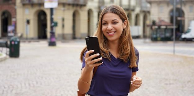 Les gens et la technologie. bannière panoramique d'une étudiante souriante et joyeuse marchant sur fond de ville de style ancien par temps nuageux.