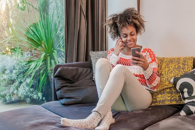 Les gens, la technologie et le concept de loisir - gros plan de la femme africaine africaine heureuse texting sur un smartphone à la maison