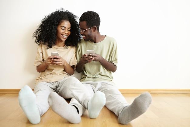 Les gens, la technologie moderne et le concept de loisirs. heureux jeune couple à la peau sombre portant des vêtements similaires se détendre sur le sol dans la chambre et à l'aide de gadgets électroniques