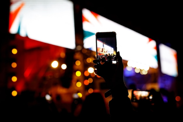 Les gens avec un téléphone portable dans les mains de l'événement de concert de tir.
