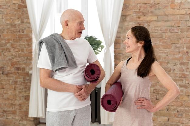 Gens de tir moyen avec des tapis de yoga