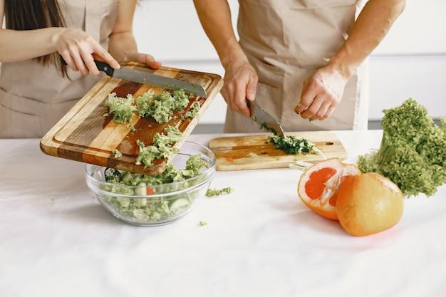 Les gens tout en préparant une salade de légumes frais. les asiatiques en tabliers.