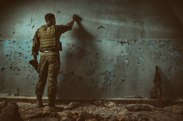 Les gens en uniforme avec des armes dans les ruines