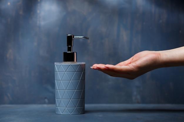 Les gens utilisent le distributeur de savon avec un capuchon en métal gris sur une table grise
