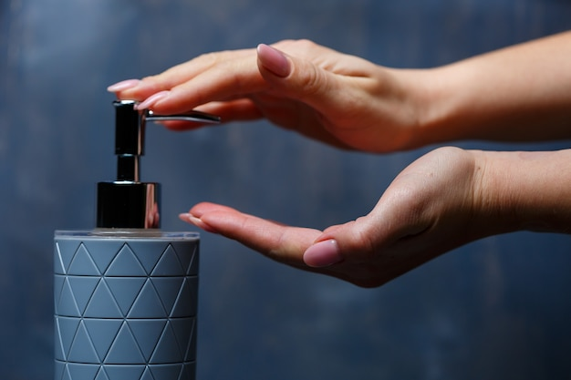 Les gens utilisent le distributeur de savon de gris sur une table grise