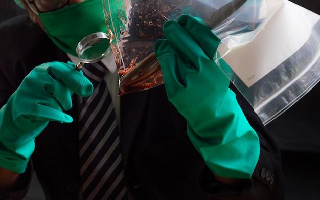 Les gens utilisent une loupe pour voir les armes et le sang dans un sac en plastique.