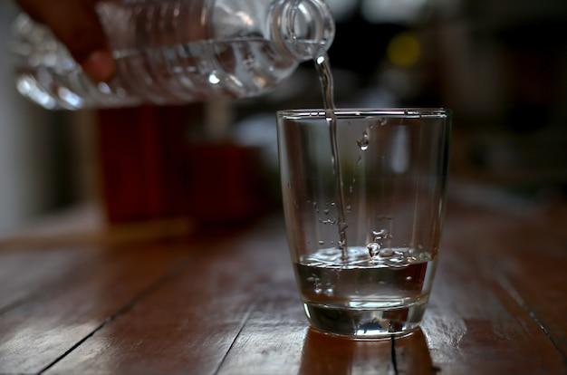 Les gens versent de l'eau dans le verre.
