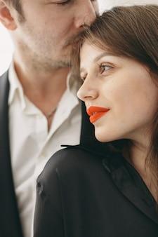 Des gens vêtus de vêtements classiques. couple élégant dans un moment sensuel sur fond blanc.