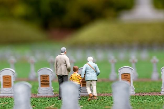 Les gens visitent le cimetière, les pierres tombales et l'herbe verte, scène miniature en plein air, en europe. mini figurines avec une grande quantité d'objets, diorama réaliste, modèle jouet