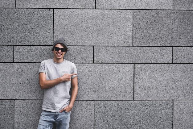 Les gens, les voyages et le tourisme - un homme avec des lunettes de soleil dans la rue de la ville et un gars montrent avec son doigt quelque chose sur fond de mur gris