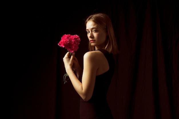 Gentil femme debout avec des fleurs roses
