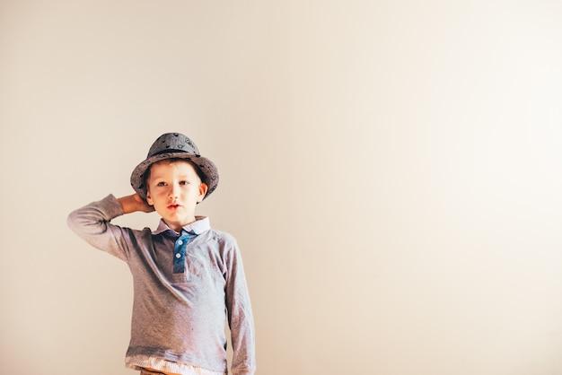 Gentil garçon jouant avec un chapeau, fond blanc