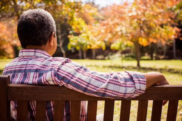 Gentil homme âgé assis seul sur un banc