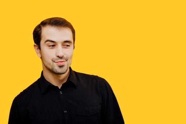 Gentil homme, regarde avec intérêt, que veux-tu? copie espace, isolé sur fond jaune, studio