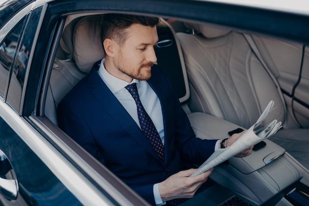 Gentil jeune directeur exécutif barbu en costume bleu foncé formel lisant le journal sur la banquette arrière de la limousine, se rend au travail à son bureau dans un centre d'affaires tôt le matin