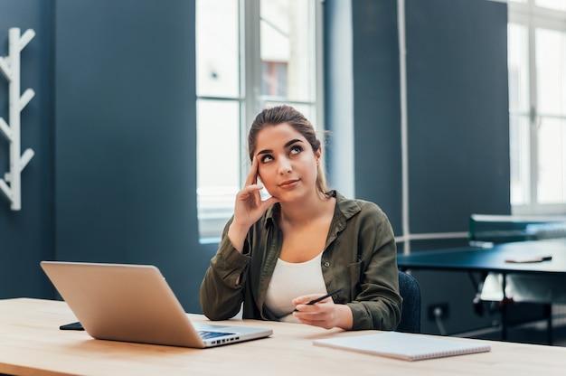 Gentil jeune femme assise sur son lieu de travail.