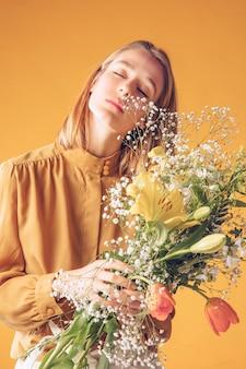 Gentil jeune femme debout avec bouquet de fleurs