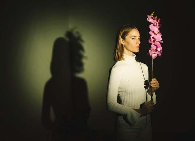 Gentil jeune femme tenant une fleur lumineuse