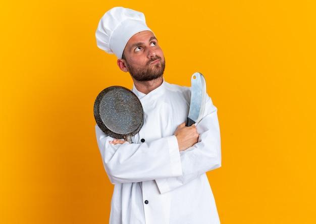 Gentil jeune homme de race blanche cuisinier en uniforme de chef et casquette debout avec une posture fermée tenant une poêle à frire et un couperet en levant