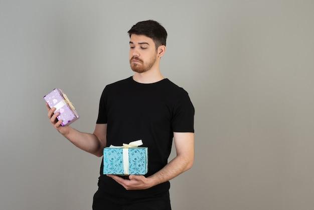 Gentil jeune homme tenant des cadeaux et le regardant.