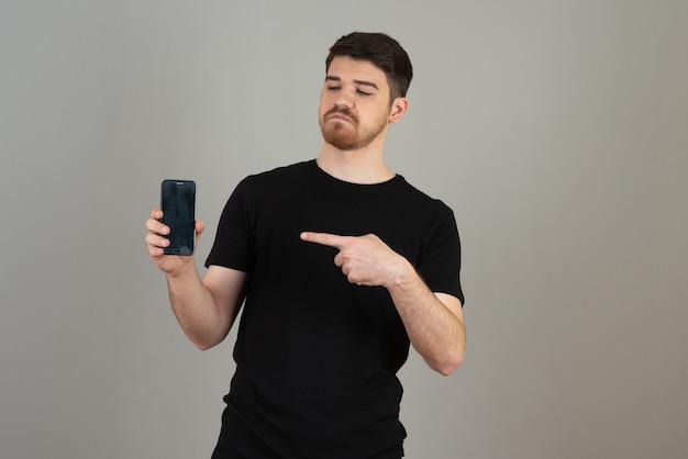 Gentil jeune homme tenant le téléphone et pointant le doigt dessus.