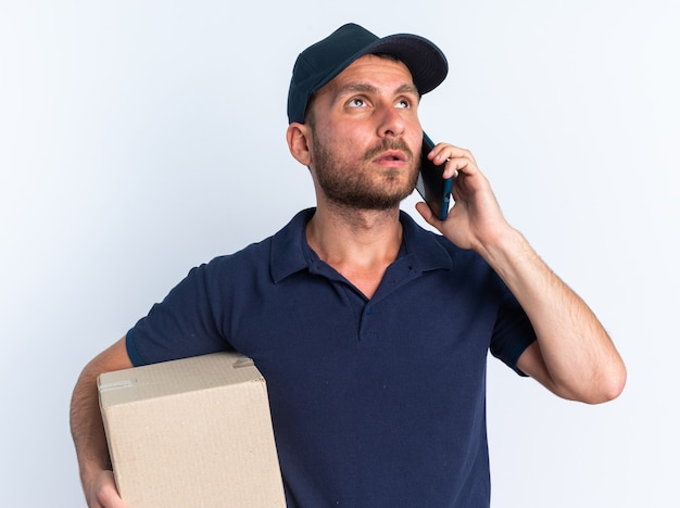 Gentil jeune livreur caucasien en uniforme bleu et casquette tenant une boîte en carton en levant parler au téléphone