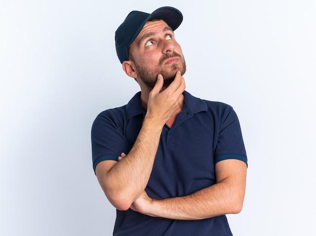 Gentil jeune livreur caucasien en uniforme bleu et casquette touchant le menton levant isolé sur mur blanc