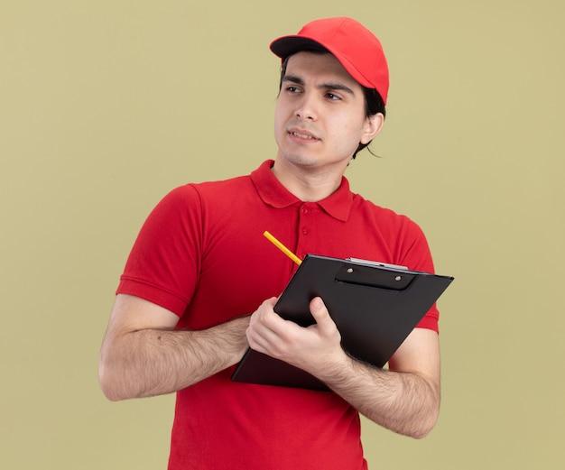 Gentil jeune livreur caucasien en uniforme rouge et casquette tenant un crayon et un presse-papiers regardant le côté isolé sur un mur vert olive