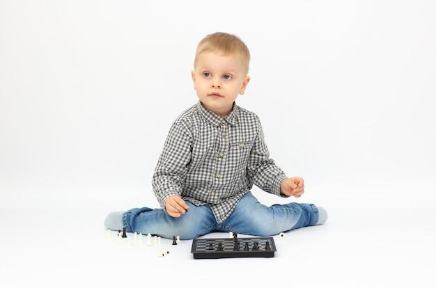 Gentil petit garçon assis sur le sol jouant aux échecs