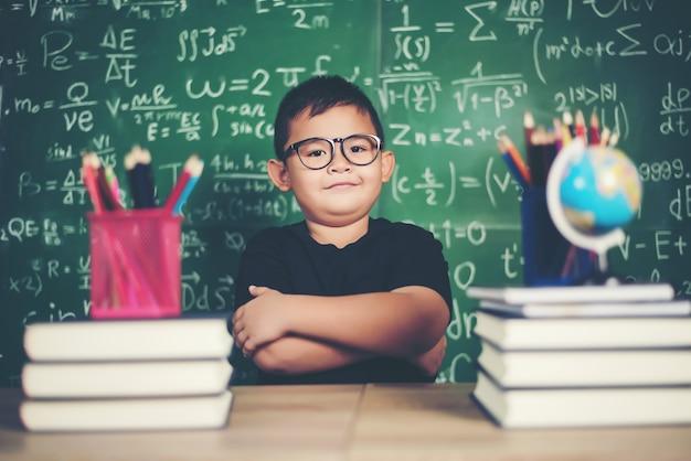 Gentil petit garçon avec livre près d'une commission scolaire