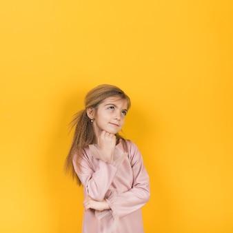 Gentil petite fille en levant sur fond jaune